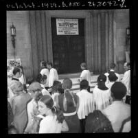 "Members of Los Angeles' St. John's Episcopal Church at church door where a sign states ""Closed for Duration of the War,"" 1970"