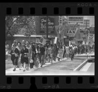 Demonstrators walking along sidewalk during Mother's Day anti-war march in Los Angeles, Calif., 1970