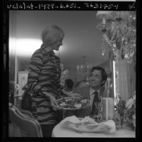 Valerie McBride serving a trout dinner to her husband, Rick in Los Angeles, Calif., 1970