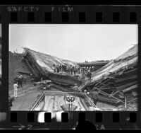 Emergency and construction workers on collapsed bridge on the San Bernardino and San Gabriel River Freeways, Los Angeles, 1970