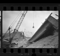 Crane with wrecking ball demolishing remains of collapsed San Bernardino Freeway bridge, Los Angeles, 1970