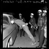 Police in riot gear arresting man during the Isla Vista riots near UC Santa Barbara, 1970