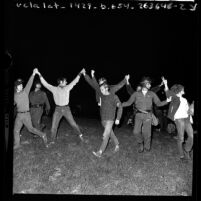 Seven men with arms up in unity being marched off by police during Isla Vista riots near UC Santa Barbara, 1970