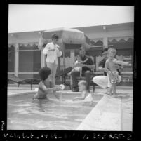 Los Angeles Dodgers' Ted Sizemore and Billy Grabarkewitz playing by a pool with their wives and children, Calif., 1970