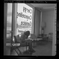 Pregnant girl hiding her face, sits filling out paperwork at abortion counseling center in Los Angeles, Calif., 1970