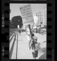 Child holding sign walks with other pickets during demonstration for Los Angeles Police officers' pay raises, 1970