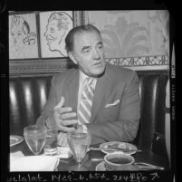 Author Louis L'Amour seated at restaurant table during interview in Los Angeles, Calif., 1970