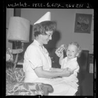 Major Lorraine R. Johnson of the Army Reserve Nurse Corps in uniform playing with her two-year-old son, 1970