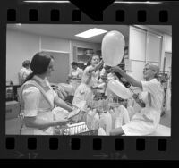 Group of Las Madrinas debutantes blowing up balloons for patients at Childrens Hospital in Los Angeles, Calif., 1970