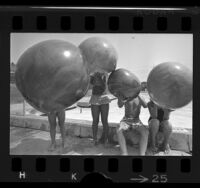 Four children hiding behind plastic balloons at Griffith Park, Los Angeles, 1970