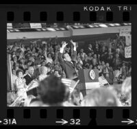 "Richard Nixon on podium with raised arms, gesturing ""V"" for victory at Republican rally in Anaheim, Calif., 1970"