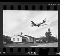 Airplane passing over a house being moved near Los Angeles International Airport, 1970