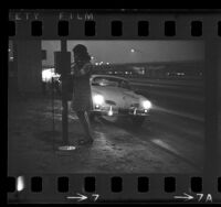Woman using a freeway emergency telephone in Los Angeles, Calif., 1970