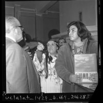 Two Native American Indian protesters talking to Dr. Carl Dentzel, director of Southwest Museum about display in Los Angeles, Calif., 1970