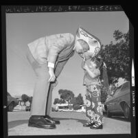 Los Angeles police recruit Robert Peterson receiving sombrero from four-year old Cynthia Ann Martinez of Wilmington, Calif., 1971