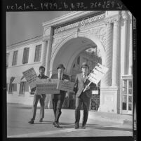 "Three Italian actors, one with sign reading ""Italians for Italian Roles"" picketing at Paramount Pictures gate in Los Angeles, Calif., 1971"