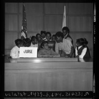 African American children from underprivileged South Central area schools on judge's bench during courthouse tour in Los Angeles, Calif., 1971
