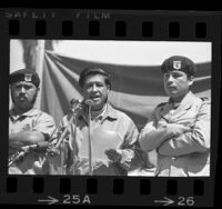 Cesar Chavez flanked by two Brown Berets, speaking at Los Angeles peace rally, 1971