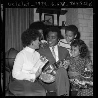 Actor Greg Morris surrounded by his family, holding his Television Father of the Year award, 1971