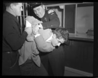 Police officers restraining actor Scotty Beckett at jail in Hollywood, Calif., 1948