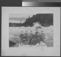 Group portrait, nine men in coats and hats, imposed on image of river rapids, 1890 [recto]