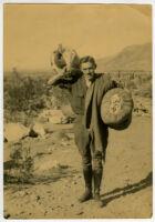 Ralph D. Cornell, holding bags, in desert