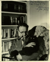 Raymond Chandler seated holding cat Taki, 1948, with inscription by Chandler to Sandoe