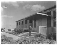 California Military Academy, exterior; boy standing in front of office building