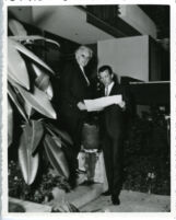 Richard J. Neutra and son, Dion outside house looking at plans [view 1]
