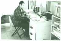Charles Kikuchi writing at desk at Gila River, AZ., circa 1943