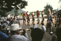 Saints Day, men in large headdresses walking and band playing, 1982
