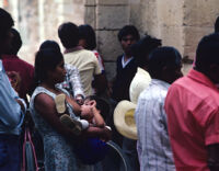 Oaxaca, woman breastfeeding toddler in crowd of men, 1982 or 1985