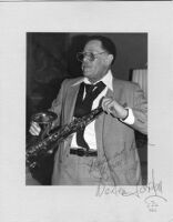 Autographed photo of Dexter Gordon with saxophone, 1979 [descriptive]
