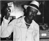 Mississippi Smokey Wilson at a cash register, 1978 [descriptive]