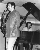 Art Pepper holding a saxophone, with Milcho Leviev in the background [descriptive]