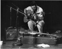 Eugene Chadbourne playing guitar, 1977 [descriptive]