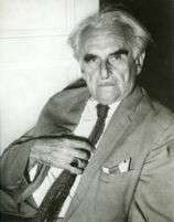 Richard J. Neutra, portrait, grey suit with hand on tie