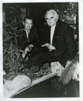 Richard J. Neutra and son, Dion sitting by pond at Research House, Silver Lake, Calif.