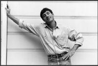 Paul Monette, portrait, demin shirt leaning against wall, circa 1988