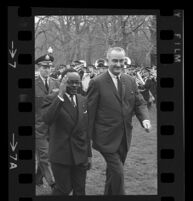 President Lyndon B. Johnson and Upper Voltian President Maurice Yaméogo with arm raised, 1965 [7]