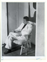 man in white suit sitting in chair