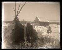 Man standing at opening of teepee; cabin in background