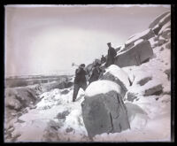 Snow covered hillside, men with sledgehammers
