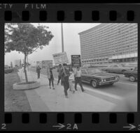 Protesters holding signs in front of the Century Plaza Hotel before Pres. Johnson's visit. 1967.