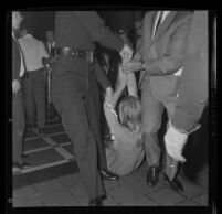 Protester Sylvia Barkley removed forcibly from City Council chambers after being denied a hearing regarding police actions at a demonstration during President Johnson's visit to Century Plaza Hotel. A. 1967.