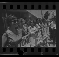 Protesters holding signs after being arraigned as a result of a clash at a demonstration at Century Plaza during President Johnson's visit, 1967.