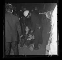 Woman sitting against police demands to disperse at demonstration at Century Plaza during President Johnson's visit, 1967.