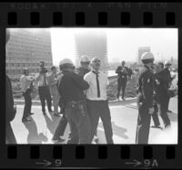 Man arrested as press watch outside of Century Plaza Hotel prior to demonstration during President Johnson's visit. A. 1967.