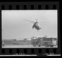 Helicopter lands near a fire engine and another helicopter, already landed, near Century Plaza during President Johnson's visit, 1967.