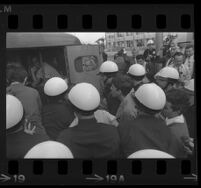 Protesters pushed into police patrol wagon after being arrested for demonstrating at Century Plaza during President Johnson's visit. B. 1967.